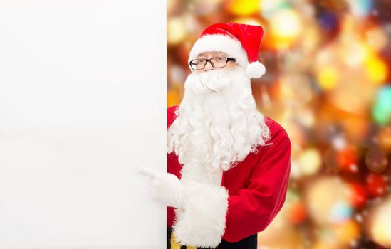 christmas, holidays, advertisement, gesture and people concept - man in costume of santa claus pointing finger to white blank billboard over red lights background