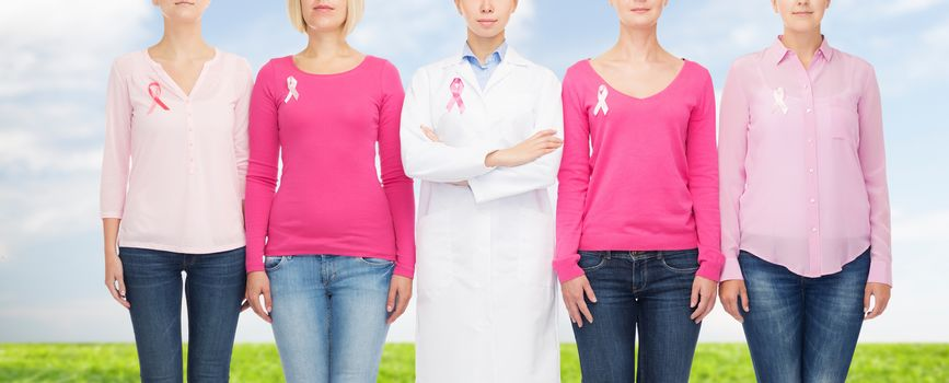healthcare, people and medicine concept - close up of women in blank shirts with pink breast cancer awareness ribbons over blue sky and grass background