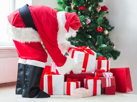 holidays, celebration and people concept - man in costume of santa claus putting present under christmas tree