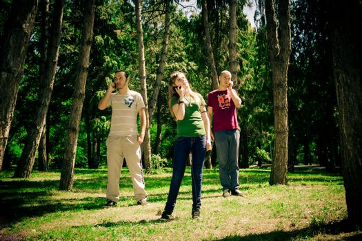 three teenagers talking to the phone in the forest