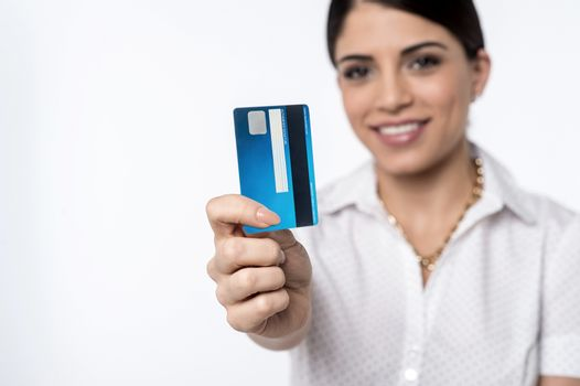 Happy woman showing credit card, focus on card.