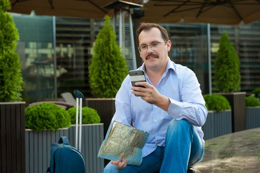 Traveler with mobile phone and city plan.