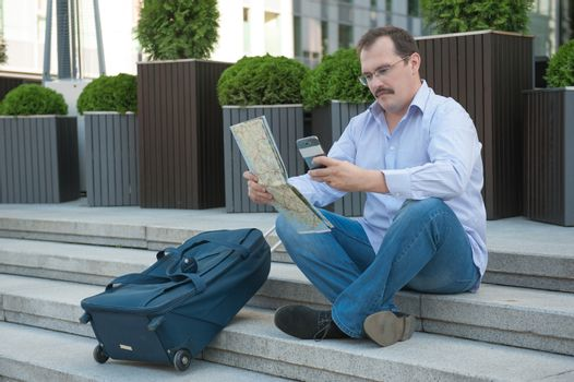 Trendy adult man in the town with touristic map outdoors.