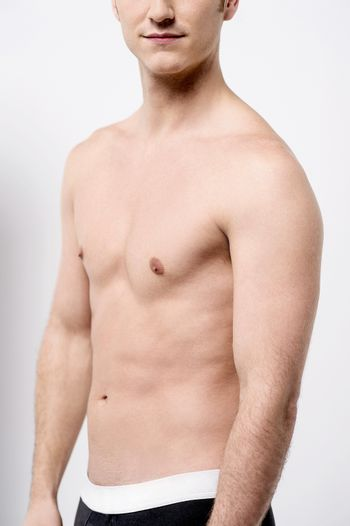 Cropped image of shirtless young male posing