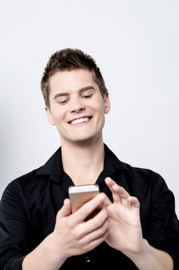 Casual young man using his smartphone over grey