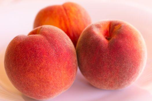 Three peaches on white