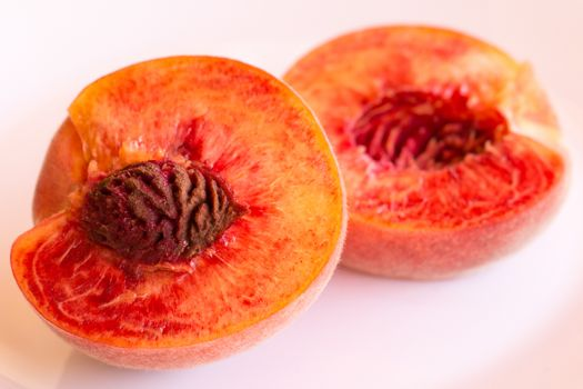 Peach cut in half on white