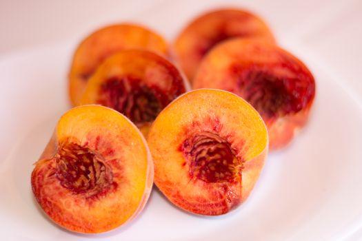 Three peaches cut in halves on white