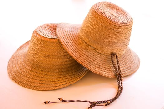Two straw hats on white
