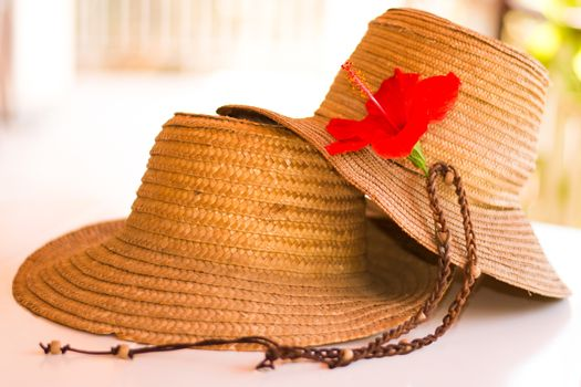 Two straw hats with an hibiscus flower