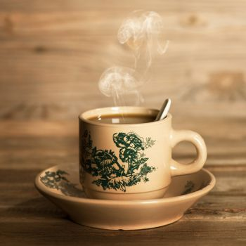Steaming traditional oriental Chinese coffee in vintage mug and