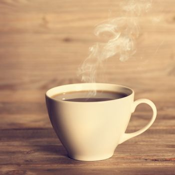 Steaming hot coffee in white cup