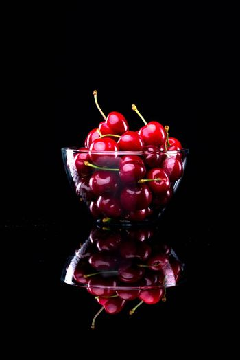 Juicy shiny cherries in a glass bowl on black background.