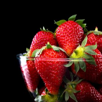 Delicious strawberries in a glass bowl on black background.