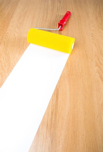 Yellow and red paint roller on hardwood floor with white copyspace paint.