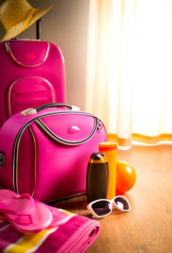 Summer vacations packing with pink trolley case, sunglasses and sun creams.