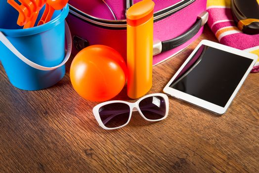 Leaving for vacations on the beach with digital tablet and colorful luggage and accessories.