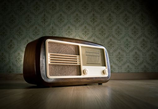 Old vintage radio on hardwood floor with retro wallpaper on background.