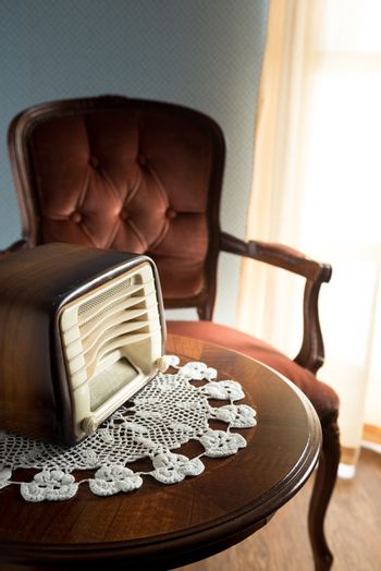 Vintage radio on round table with doily and living room on background.