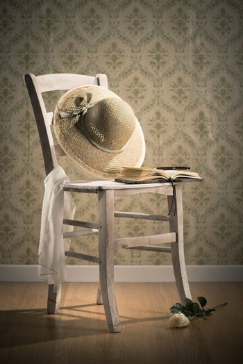 Old open book and straw hat on a shabby chic chair and rose on floor.