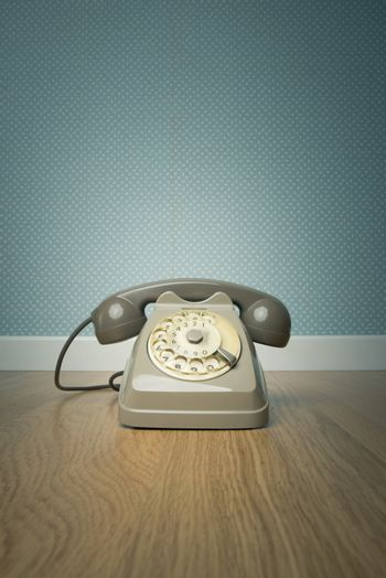 Gray vintage phone on hardwood floor and dotted light blue wallpaper on background.