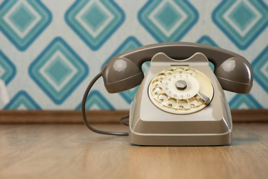 Vintage gray telephone on hardwood floor, diamond light blue retro wallpaper on background.