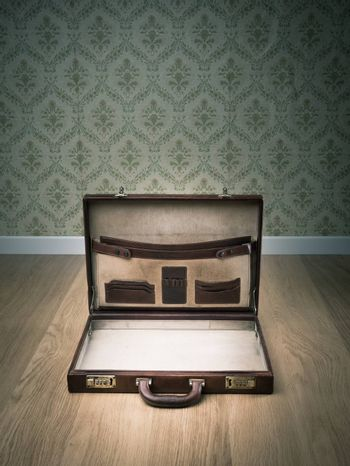 Open vintage leather briefcase on hardwood floor, retro wallpaper on background.
