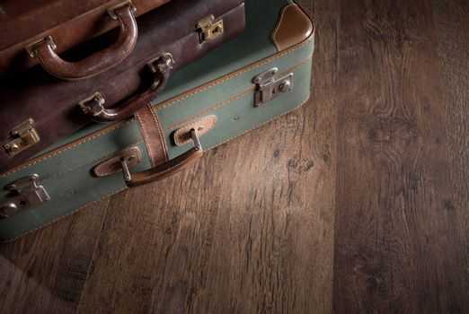 Vintage luggage close-up on dark hardwood floor, travelling concept.