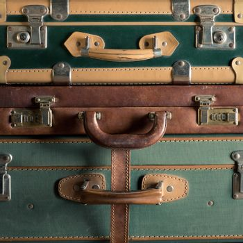 Stack of colorful vintage suitcases, handles close up, travelling concept.