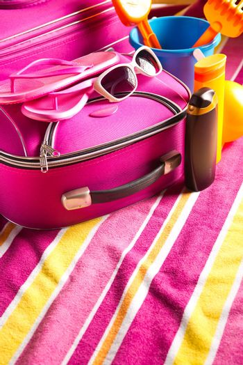 Striped colorful towel with pink bag, sunglasses and sun creams.