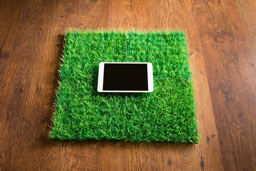 Blank ipad on squared artifical grass tile lying on hardwood floor.