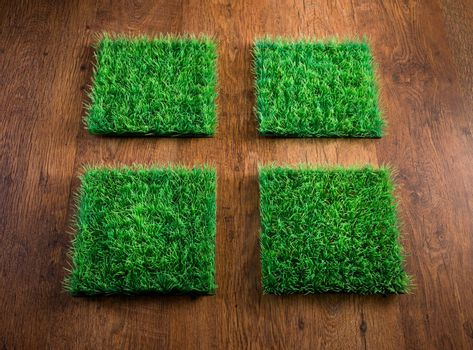 Four artificial turf tiles on hardwood floor, environmental care concept.