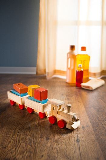 Wooden toy train with wood cleaner products on parquet next to a window.