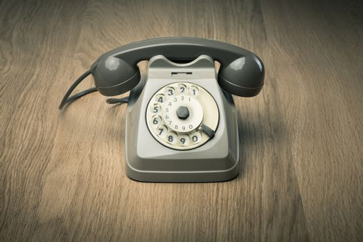 Vintage gray telephone on hardwood surface desk or floor.