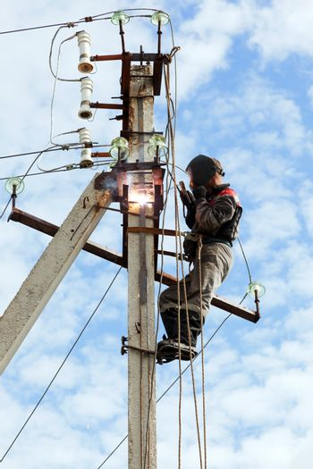 Electrician connects welding metal parts ground loop on a pole transmission line