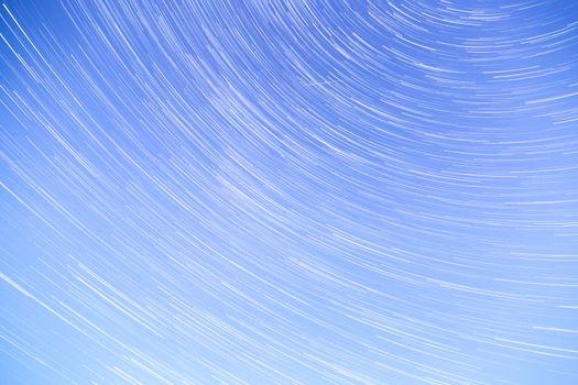 Star Trails streaking across a Blue Sky.