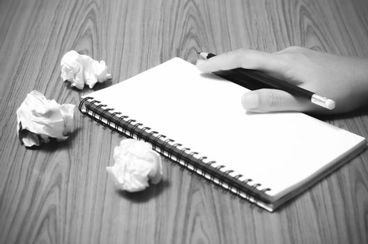 hand writing on notebook with crumpled paper black and white col