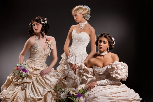 Three young beautiful women in wedding dresses
