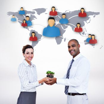 Composite image of business colleagues holding plant and looking at camera