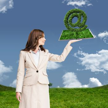 Woman holding lawn book against grass and sky