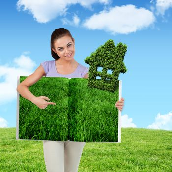 Woman pointing lawn book against blue sky over green field