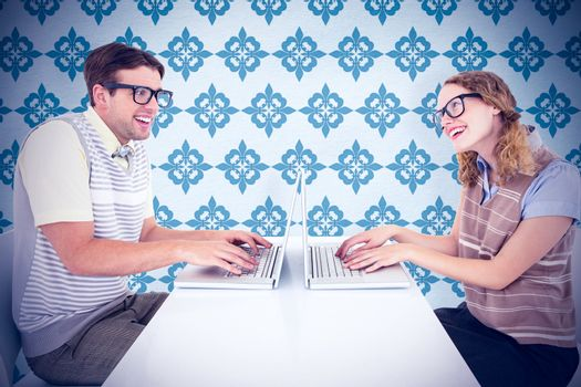 Geeky hipster couple using laptop against blue background