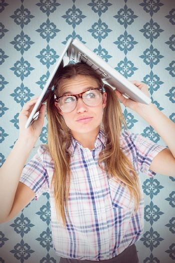 Geeky hipster holding her laptop over her head  against blue background