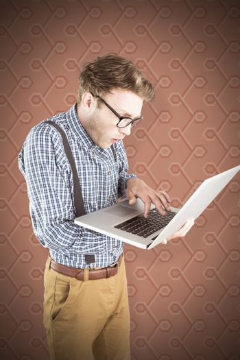 Geeky businessman using his laptop against background