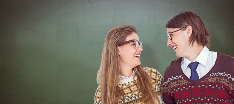 Happy geeky hipster couple looking at each other against green chalkboard