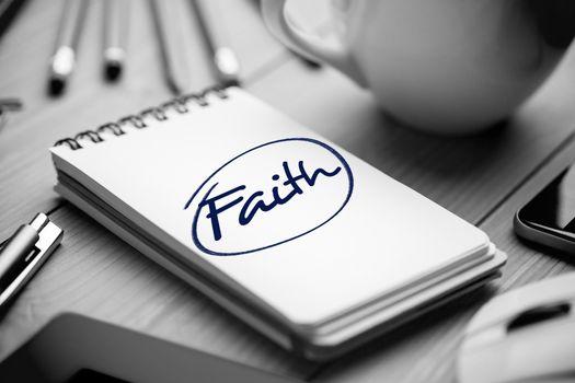 Faith against notepad on desk
