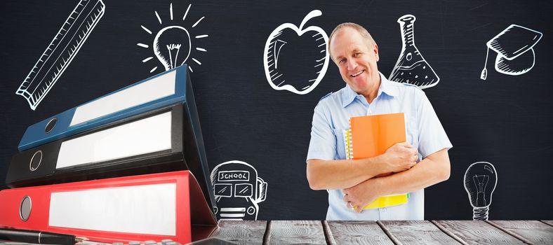 Mature student holding notebooks against blackboard