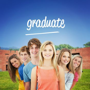 The word graduate and smiling group standing behind one another at various angles against students using laptop in lawn against college building