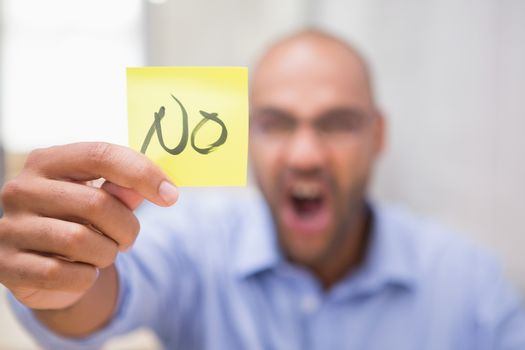 Businessman holding paper that says NO