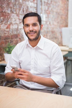 Businessman text messaging at desk